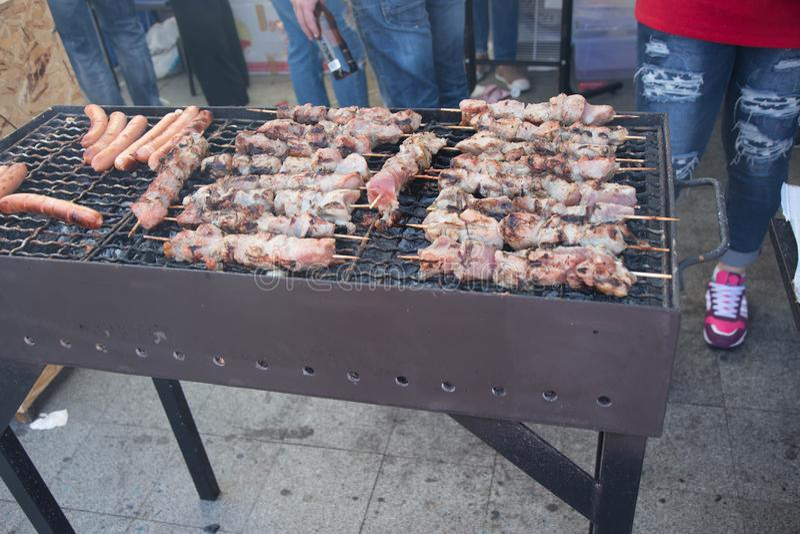 Man att grilla ett sortiment av kött och kebaber på en bärbar grillfest som lyfter en köttbiff med ett par av tång royaltyfri fotografi