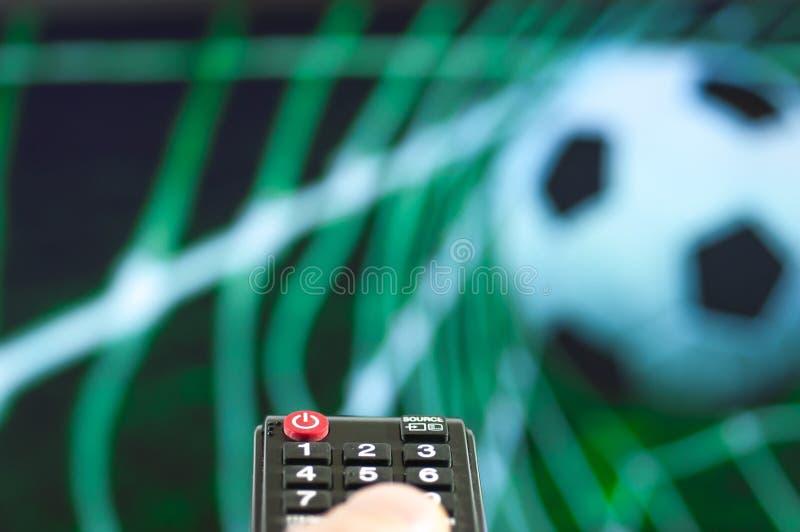 Man att hålla ögonen på fotbollleken framme av tv royaltyfria foton
