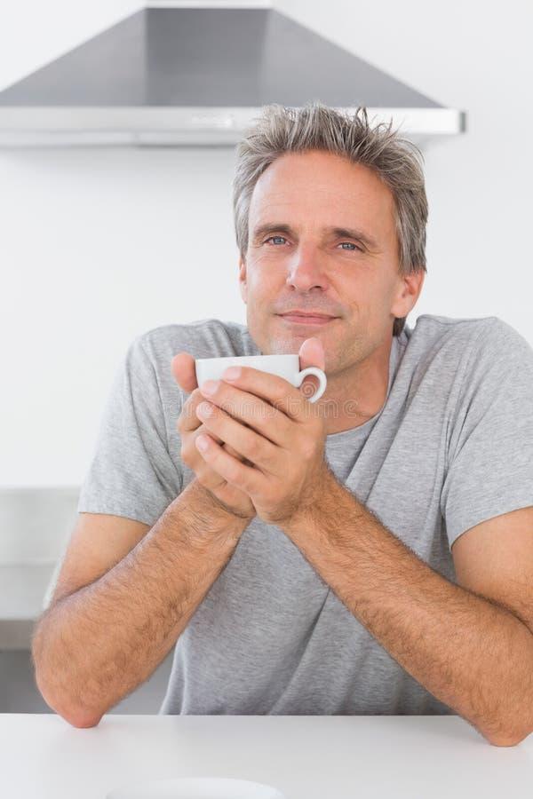 Man att ha kaffe i kök i morgonen royaltyfria bilder