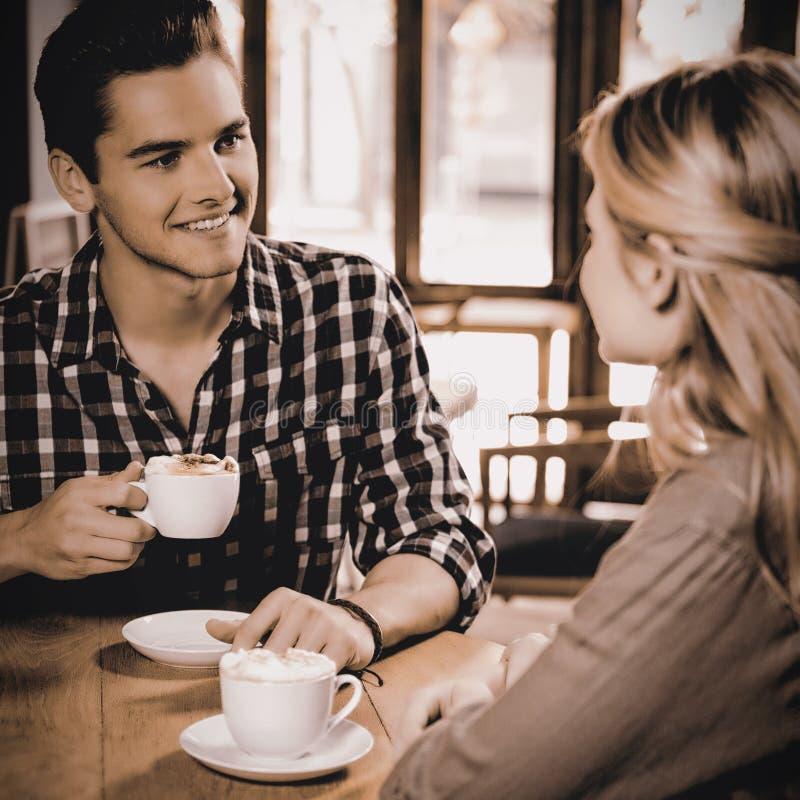 Man att ha kaffe, medan tala med kvinnan i kafé fotografering för bildbyråer