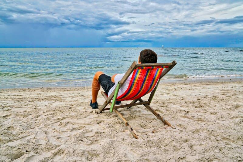 Man att ha picknick och att förbise havssammanträdet på en röd stol på stranden arkivbilder