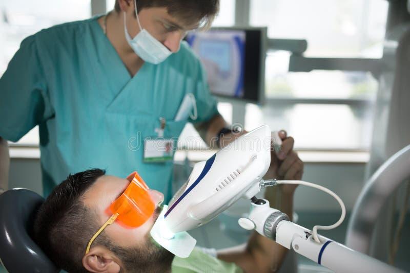 Man att ha tänder som gör vit vid den tand- UV blekmedelapparaten, den tand- assistenten som tar omsorg av patienten Ögon som sky royaltyfri bild
