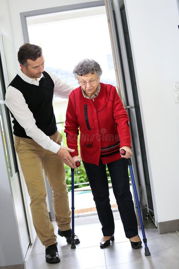 Man att hjälpa en äldre dam som skriver in huset arkivbilder