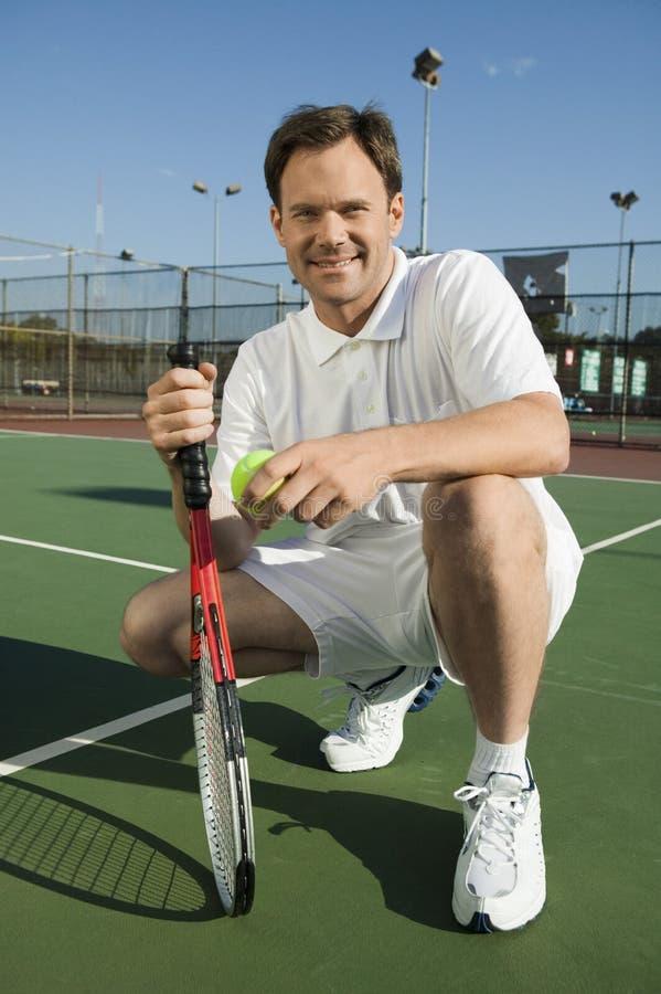 Man att huka sig ned på hållande tennisracket för tennisbanan och klumpa ihop sig ståenden royaltyfri foto