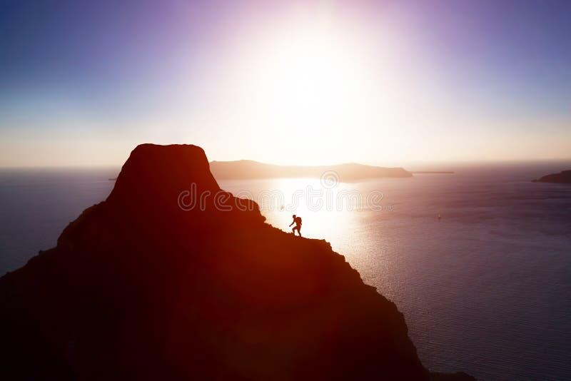 Man att klättra upp kullen för att nå maximumet av berget över havet arkivbilder