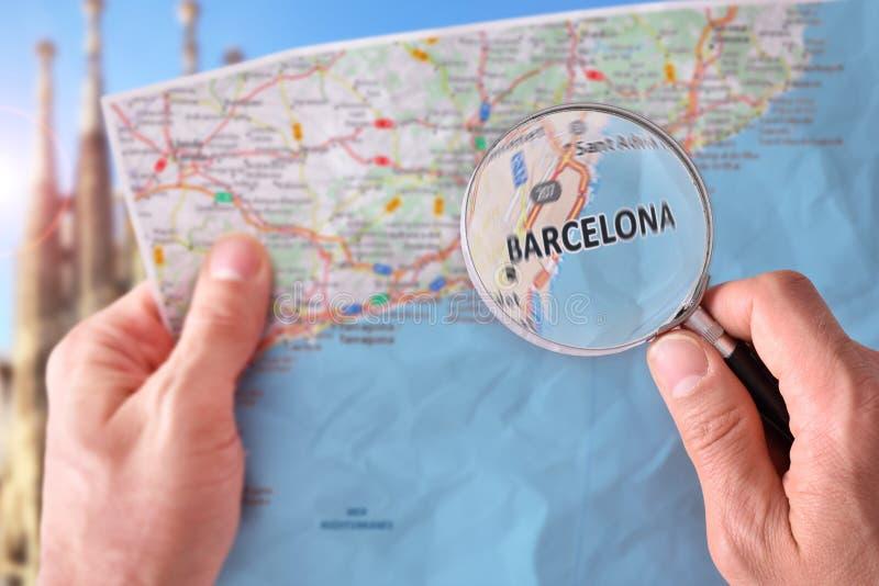 Man att konsultera en översikt av Barcelona med ett förstoringsglas fotografering för bildbyråer
