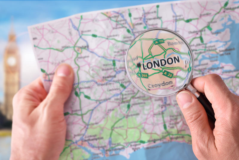 Man att konsultera en översikt av London med ett förstoringsglas royaltyfri foto