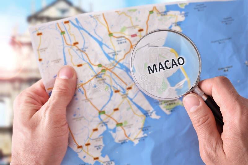 Man att konsultera en översikt av Macao med ett förstoringsglas royaltyfri bild