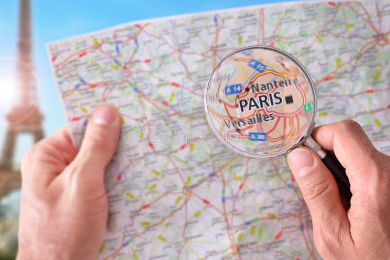 Man att konsultera en översikt av Paris med ett förstoringsglas arkivfoton