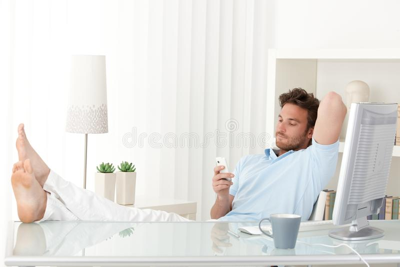 Man att koppla av på skrivbordet som texting på telefonen arkivbilder