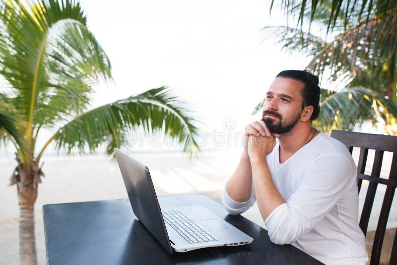 Man att koppla av på stranden med bärbara datorn, freelancerarbetsplatsen, dröm- jobb arkivfoton