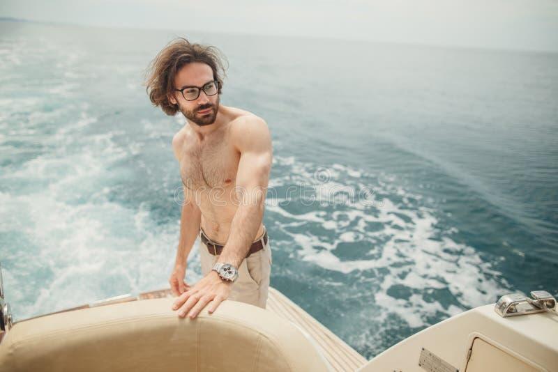 Man att koppla av under solen som ligger på ett fartyg på havet Lyxig semester på en yacht i öarna arkivbild