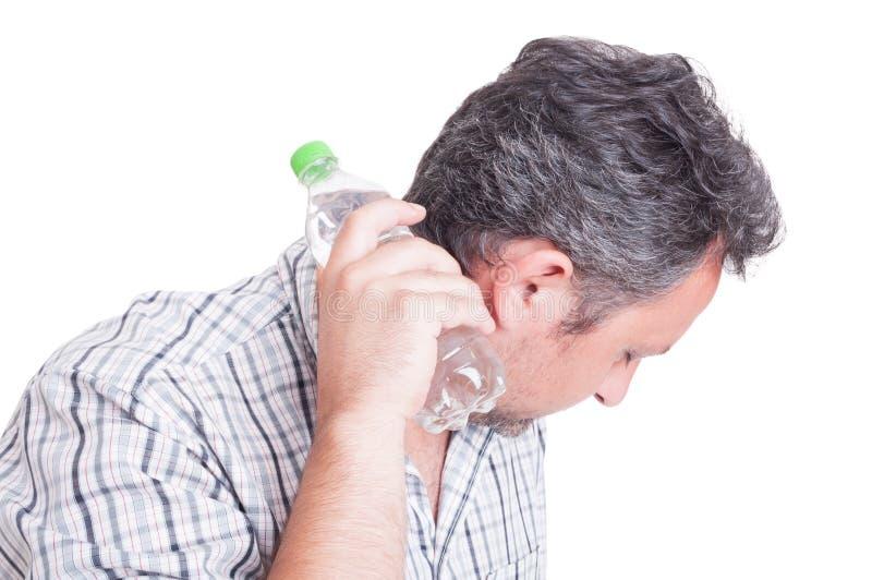 Man att kyla ner med en flaska av kallt vatten arkivfoto