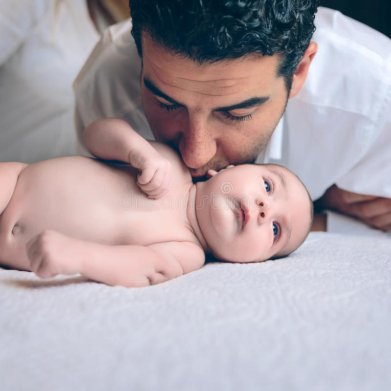 Man att kyssa till fridsamt nyfött ligga över säng arkivbilder