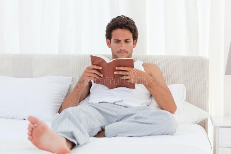 Man att läsa en bok på hans underlag fotografering för bildbyråer