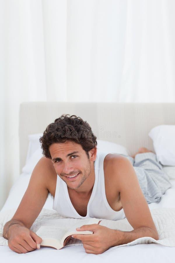 Man att läsa en bok på hans underlag royaltyfria foton