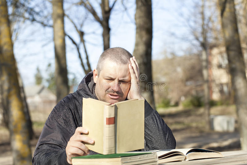 Man att läsa en bok utomhus på en bänk royaltyfri fotografi