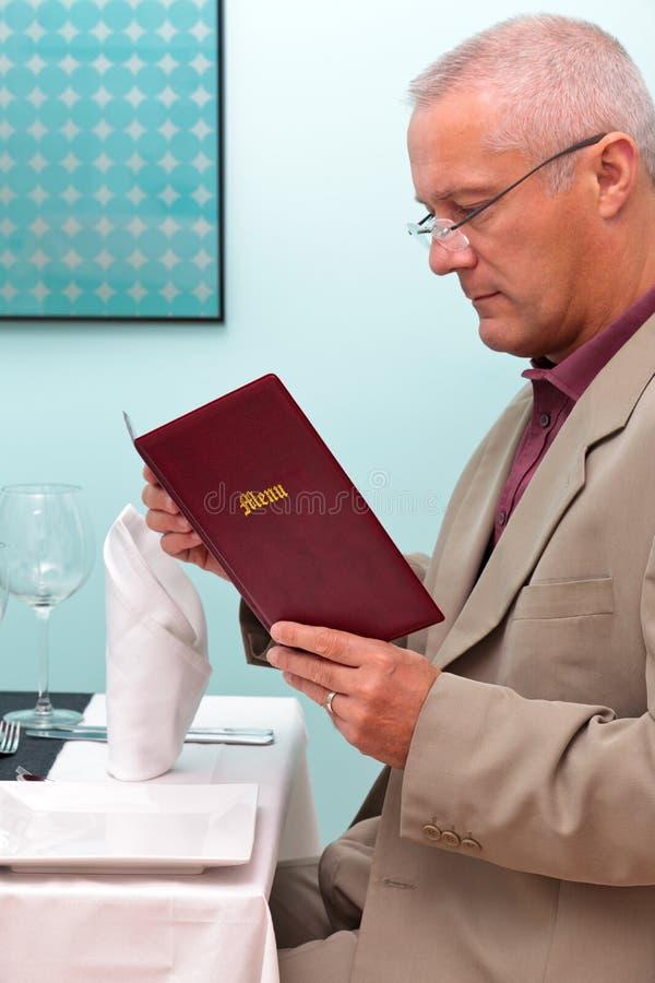 Man att läsa en meny i en restaurangvertical royaltyfri foto