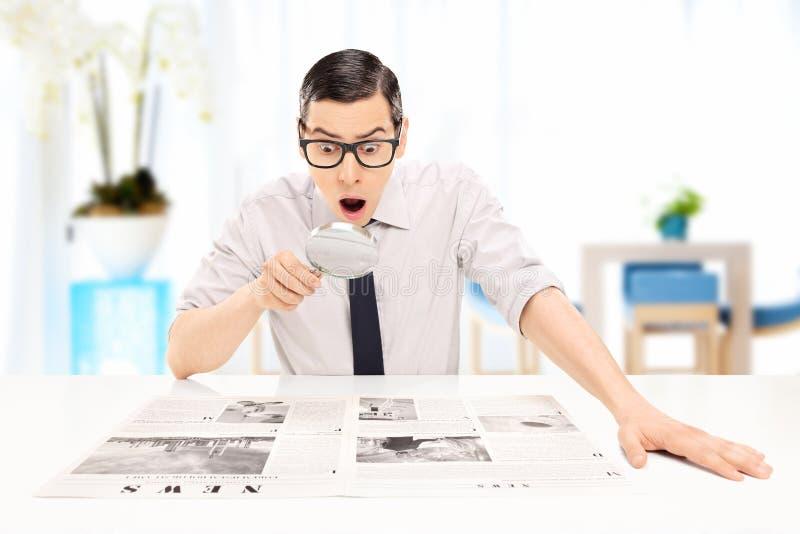 Man att läsa nyheterna med noggrann undersökning i ett kontor arkivbilder