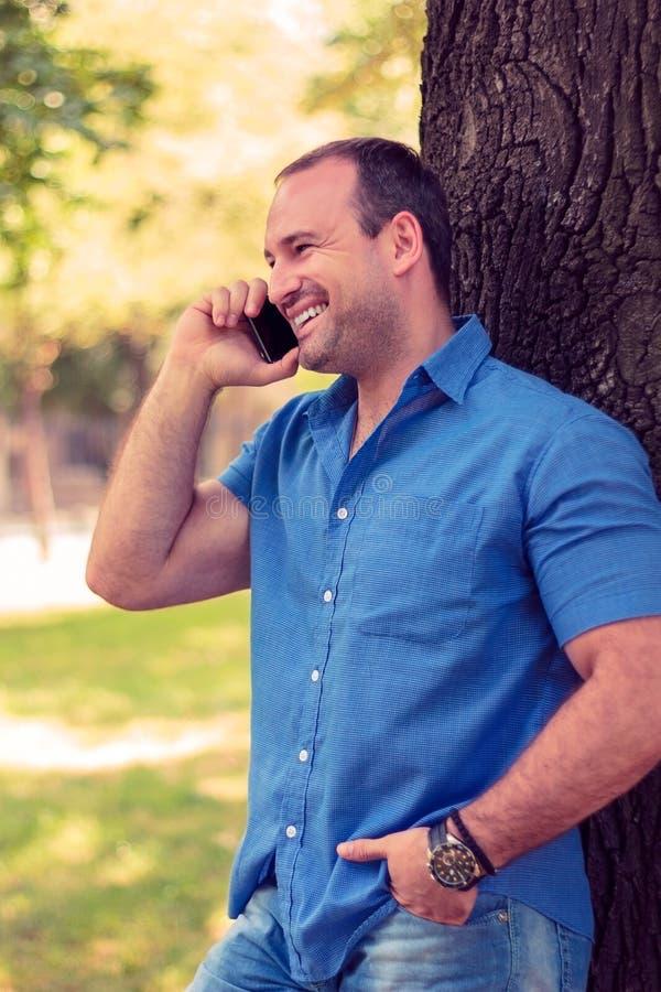 Man att le på telefonen i en parkera arkivbilder