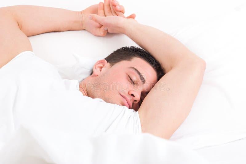 Man att ligga i säng och att ha söta drömmar, medan sova fotografering för bildbyråer