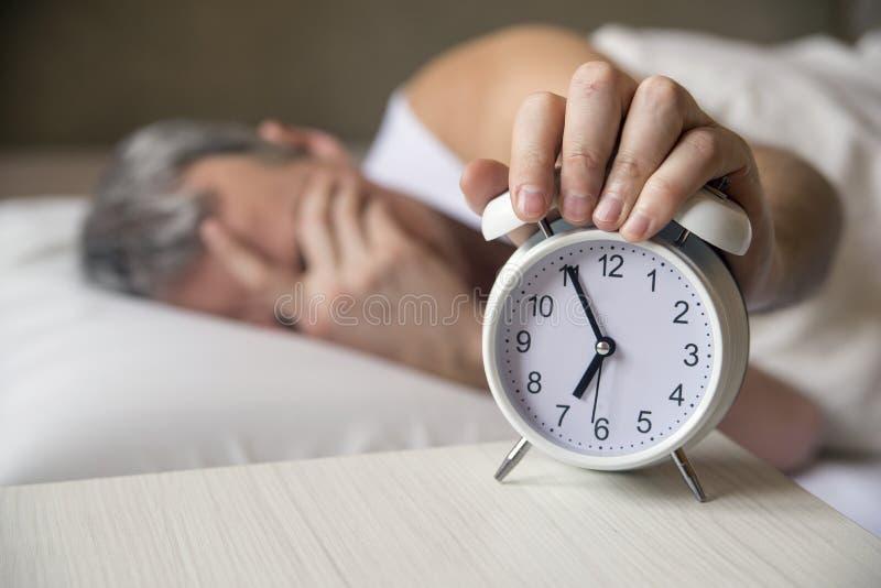 Man att ligga i säng som är roterande av en ringklocka i morgonen på 7am Attraktiv man som sover i hans sovrum royaltyfri fotografi