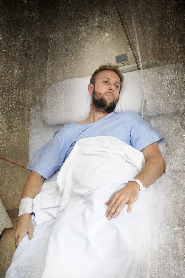 Man att ligga i sängsjukhusrum som vilar från, smärtar bekymrat om dåligt vård- villkor royaltyfria bilder
