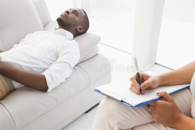 Man att ligga på soffan som talar till hans terapeut arkivbild