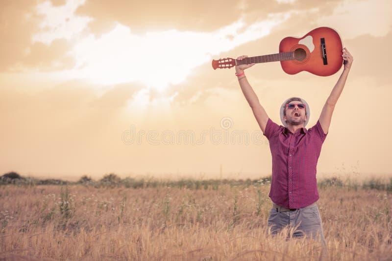 Man att lyfta gitarren upp i luften i vetefält royaltyfri foto