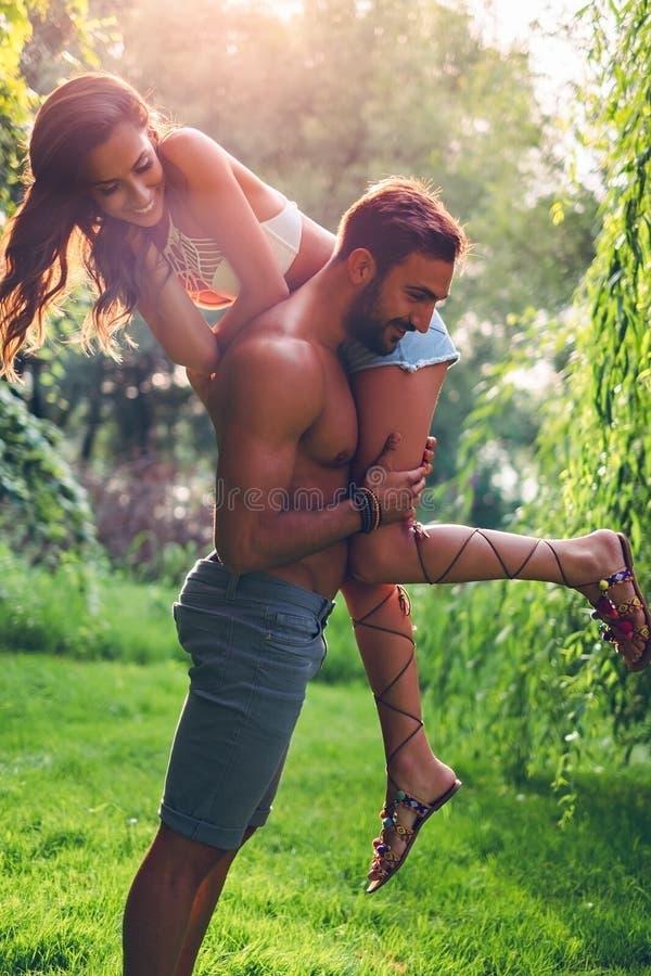 Man att lyfta upp hans flicka, medan hon kämpar arkivfoton