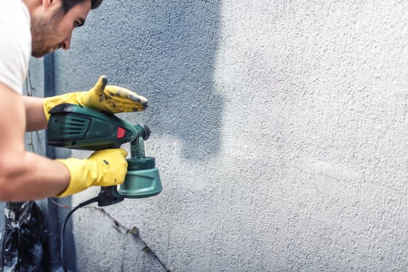 Man att måla en grå vägg som renoverar yttre väggar av det nya huset royaltyfria foton