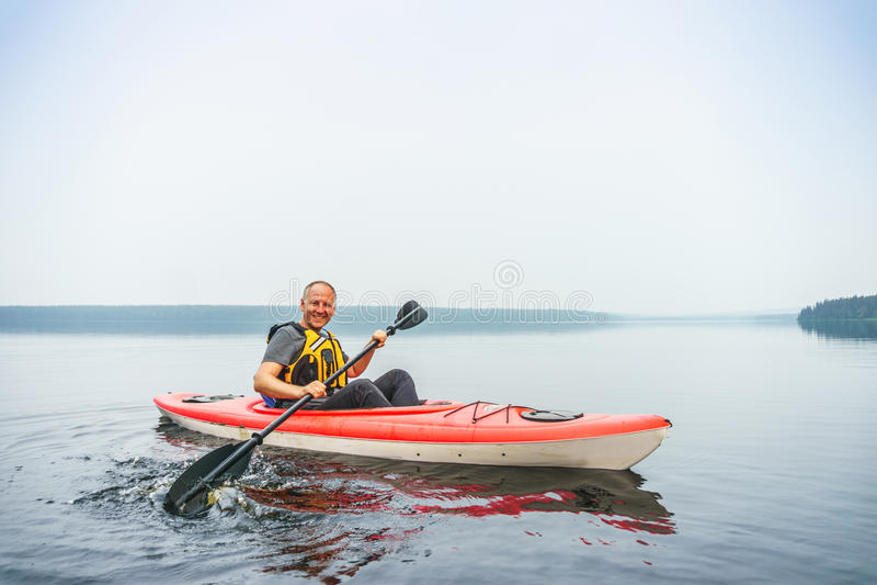 Man att paddla i kajaken på en stillhet, den dimmiga sjön arkivfoton