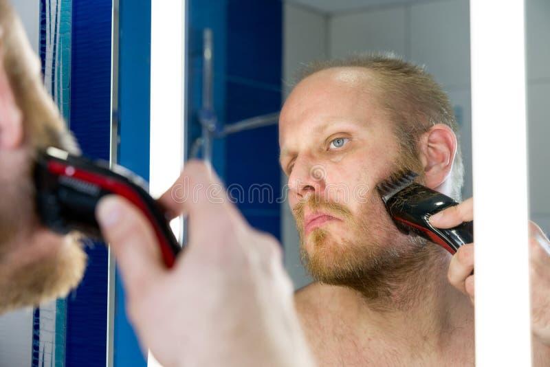 Man att raka och att se in i spegeln royaltyfria foton