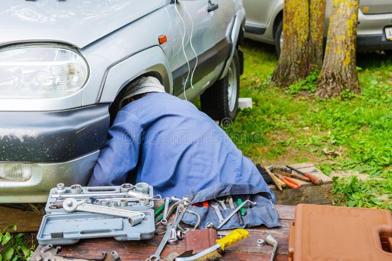 Man att reparera den främre upphängningen av bilen i fältet royaltyfri foto
