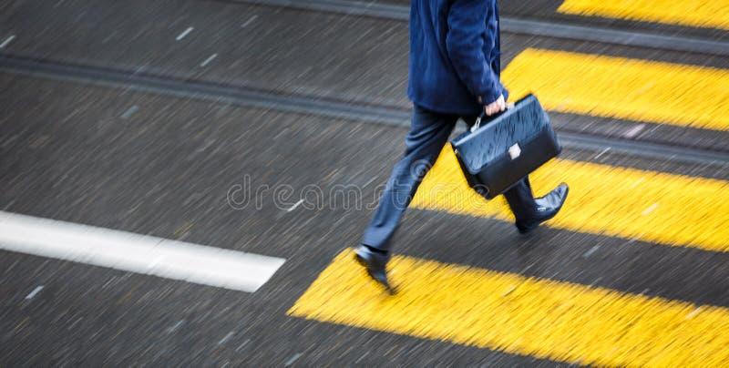 Man att rusa över en vägkorsning i en stad på en regnig dag arkivfoton