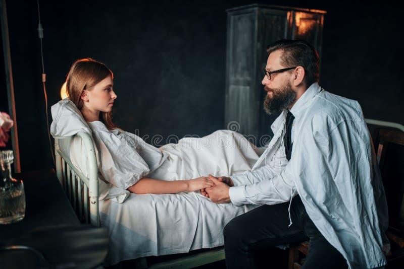 Man att rymma en hand av den sjuka älskade kvinnan i säng royaltyfri fotografi