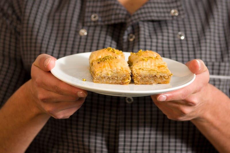 Man att rymma en läcker traditionell turkisk matbaklava med pistaschen i hans händer arkivfoto