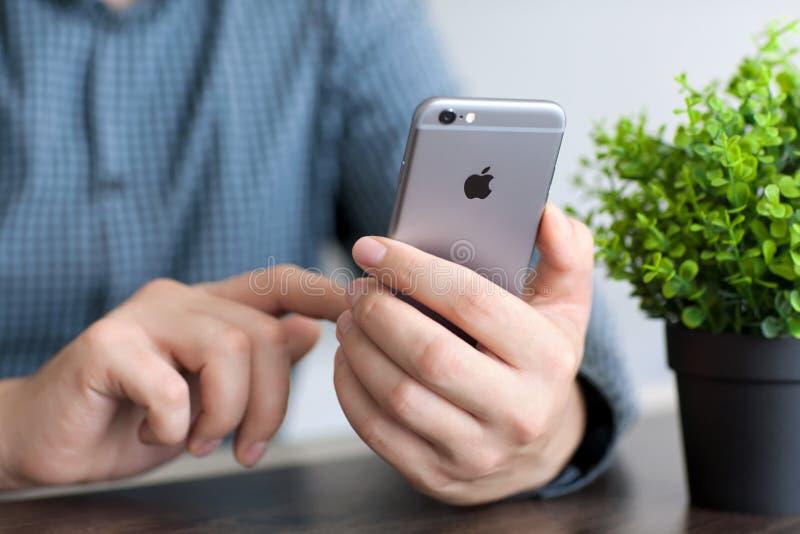 Man att rymma en ny iPhone 6 utrymmegrå färger royaltyfria foton