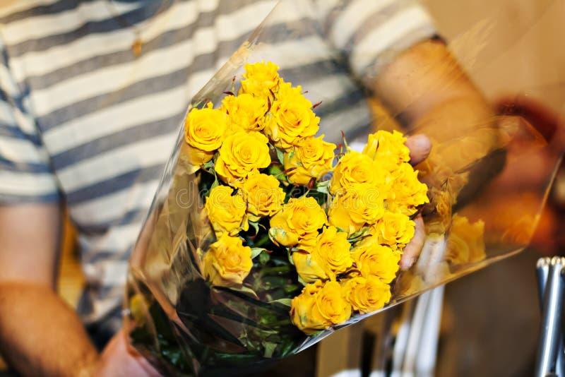 Man att rymma en stor bukett av gula rosor royaltyfri bild