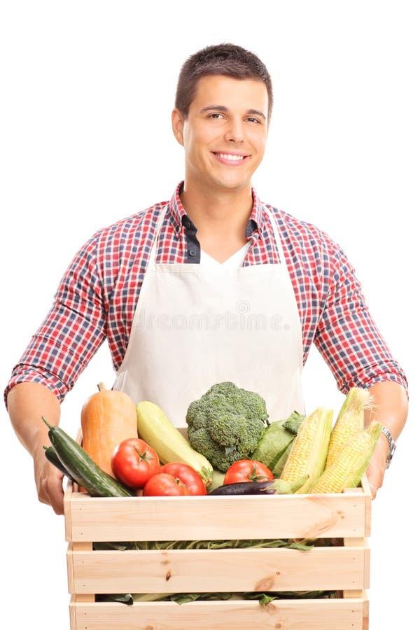 Man att rymma en träspjällåda full av grönsaker arkivfoton
