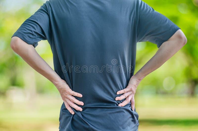 Man att rymma hans baksida smärtar in, det monokromma fotoet med rött som en sym arkivfoton