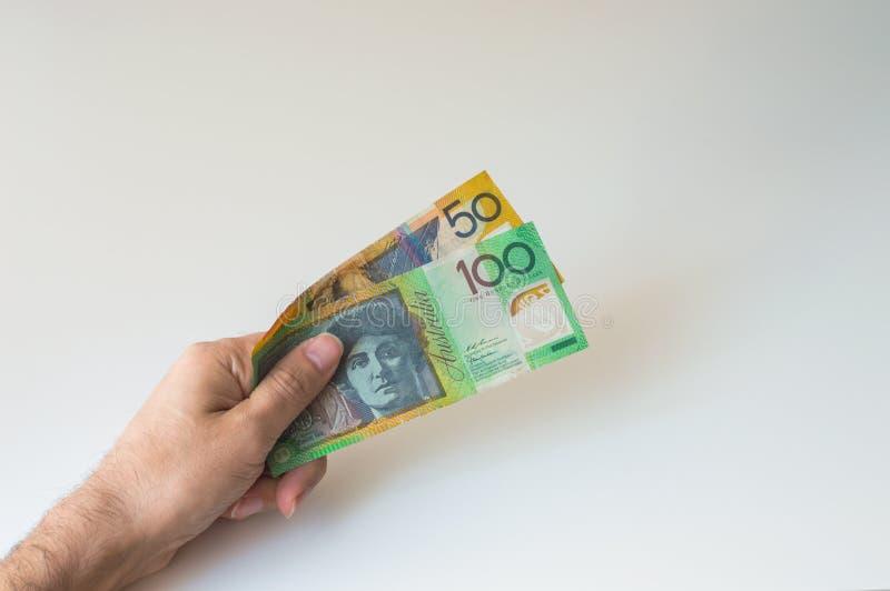 Man att rymma hundra och femtio australiska dollar i hans royaltyfri bild