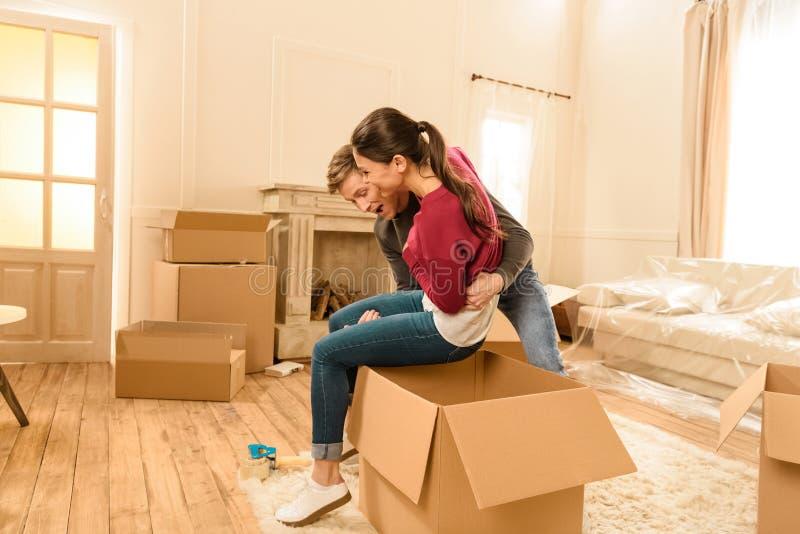 Man att sätta kvinnan in i kartongen på det nya hemmet royaltyfri foto
