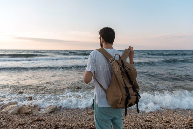 Man att sätta på en ryggsäck på bakgrunden av havet arkivfoton