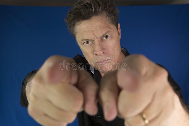 Man att se direkt på dig med hans nävar som ska slåss royaltyfri foto