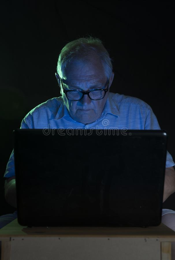 Man att se en datorskärm på natten arkivfoton