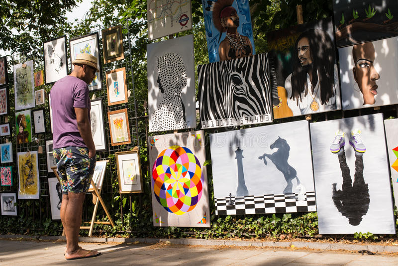 Man att se en målningutställning i en London gata arkivfoton
