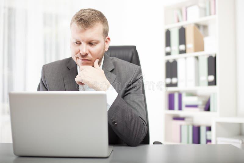Man att se hans bärbar dator med ett tvunget uttryck royaltyfri fotografi