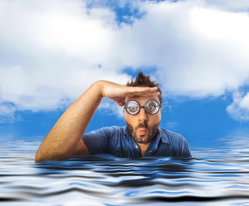 Man att se långt borta i vattnet av havet arkivfoto