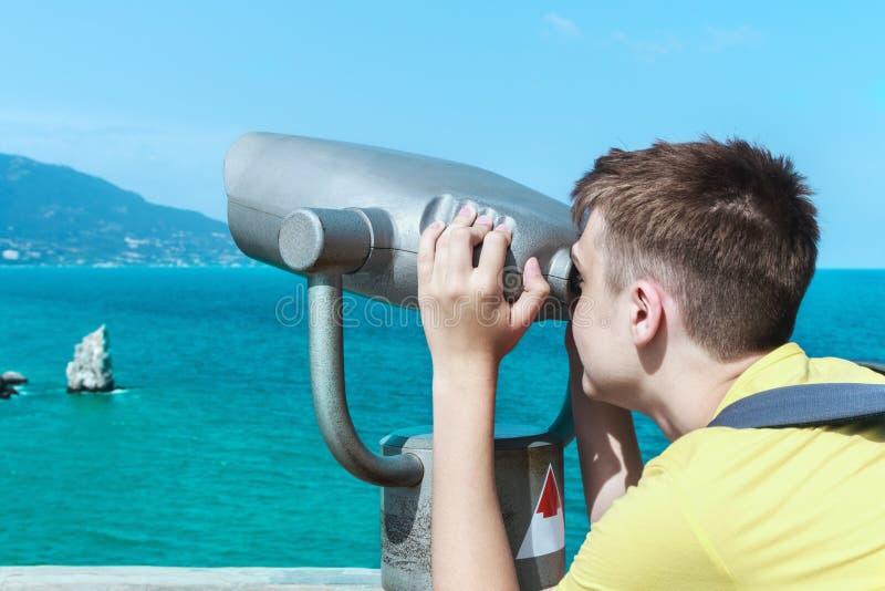 Man att se till och med kikare på bergen och havet royaltyfri foto